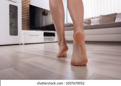 Low Section View Of An Foot Walking On Heated Hardwood Floor
