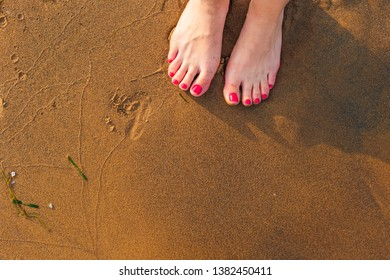 Low section view of a young woman legs standing on sand on the beach. Shadows of feet on sand
