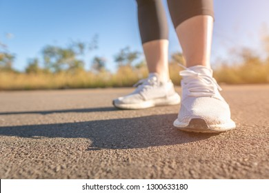 Low Section Of Woman Exercising On Road
