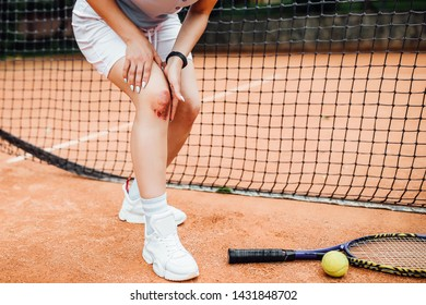 Low section of  woman holding tennis racket while suffering from knee pain on red tennis court during summer..