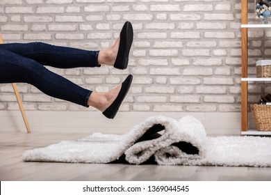 Low Section Of Woman Legs Stumbling With A Carpet At Home