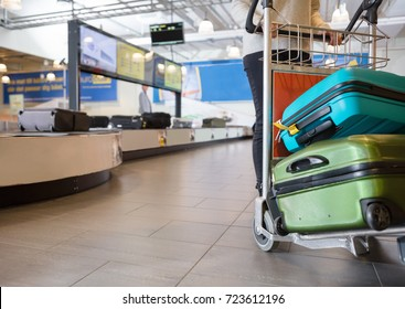 Low Section Of Woman With Luggage In Trolley At Airport