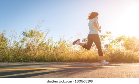 Low Section Of Woman Running On Road