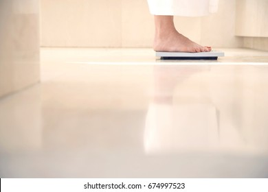 Low section of woman standing on weighing scale in bathroom