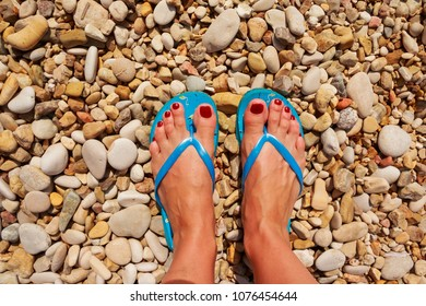 Low section of woman wearing slippers while standing on board walk.First person perspective, view on own feet. Rocky beach.Female legs wearing flip flops near sea. top view