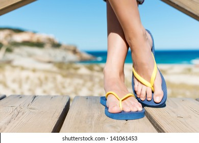 Low section of woman wearing slippers while standing on board walk