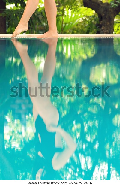 Low section of woman's legs by poolside feeling the water temperature