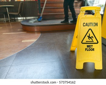 Low Section Of Worker Mopping Floor With Wet Floor Caution Sign On Floor