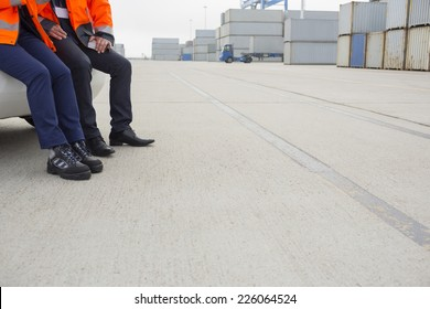 Low section of workers leaning on car in shipping yard