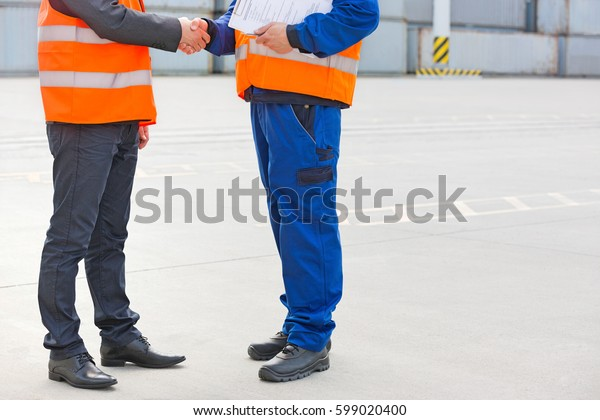 Low section of workers shaking hands in shipping yard