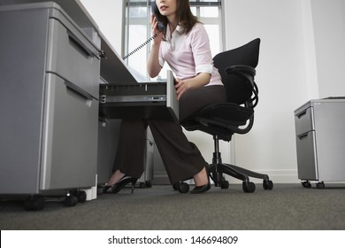 Low section of young businesswoman talking on telephone while opening drawer in office