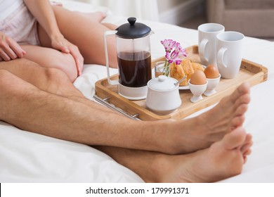 Low section of a young couple having breakfast in bed at home
