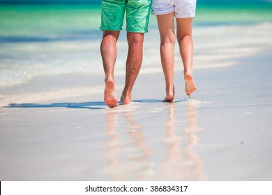 Low section of young couple on white beach at tropical vacation