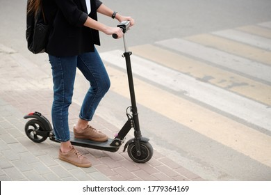Low section of young female in blue jeans and black jacket keeping one leg on electric scooter while standing by road with crosswalk
