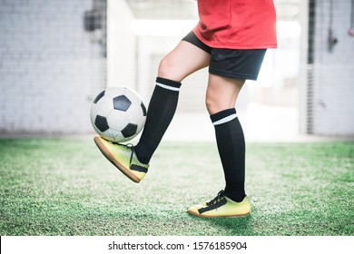 Low section of young female football player with soccer ball over foot standing on green field during training