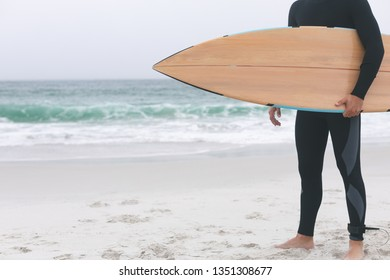 Low section of young male surfer holding surfboard on the beach