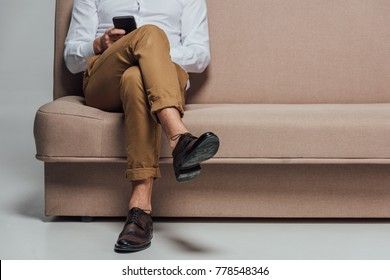low section of young man using smartphone while sitting on sofa isolated on grey