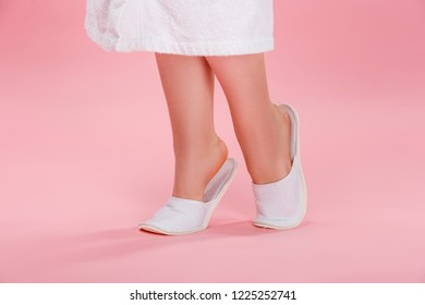 low section of young overweight woman in white slippers and bathrobe on pink 9ac7bab2e