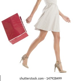 Low section of young woman walking with shopping bag isolated over white background