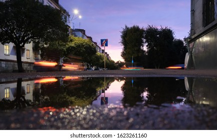 Low shot of puddle whilst it rains with city traffic