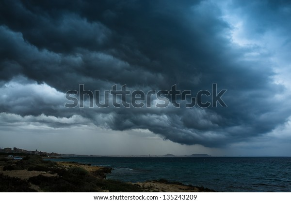 Low threatening  storm clouds hanging over a coastal area