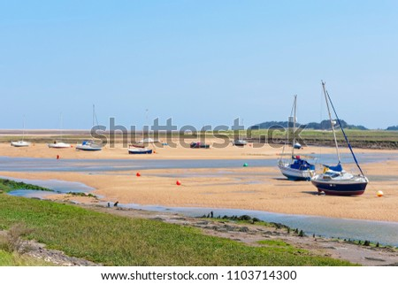 Low tide in the estuary at Wells-next-the-Sea. Small yachts sit at an angle beached on the sand.