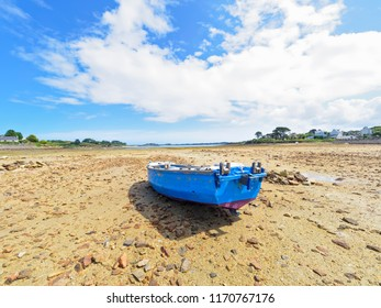 Low tide in Kermengi, Brittany, harbour. A small rowing boat rests on the rocky harbour floor.