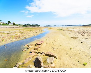 At low tide, in Kermengi harbour, Brittany, a small stream winds its way to the sea.