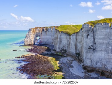 """Low tide landscape featuring the """"The Manneporte"""" natural stone arch, closed to Etretat in Normandy, France."""