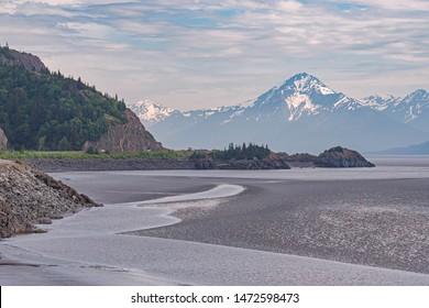 the low tide mudflats of the turnagain arm of cooks inlet in alaska with the Chugach Mountains in the background