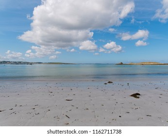 Low tide on a beach in Landeda, Brittany. A long white cloud softens the sunligh.
