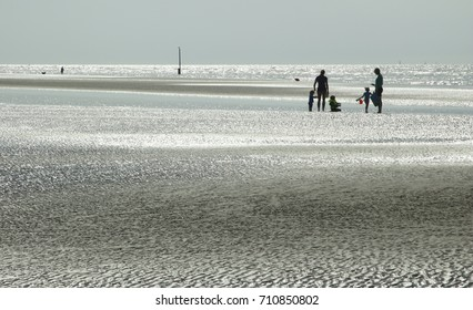 Low tide. Reflections and shadows on a summer evening at the beach of Nieuwpoort Belgium