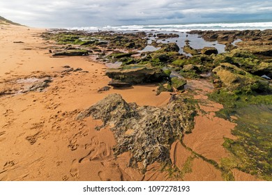 Low tide rocky beach waves and ocean against blue cloudy sky seascape in Garvies beach, Bluff,  Durban, South Africa