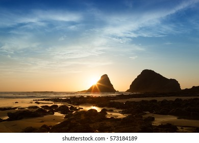 Low tide shows off the lava rock beach at sunset on Heceta Head beach, Oregon in the great Pacific Northwest.