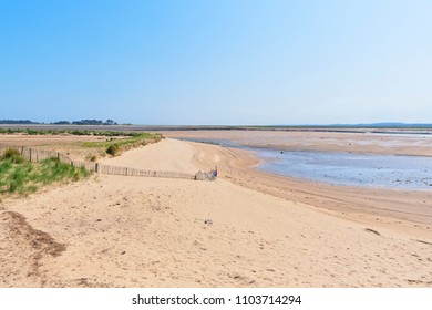 At low tide a small beach borders the estuary in Wells-next-the-Sea. Beyond at the salt marshes and a small wood.