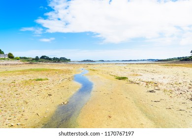 Low tide and a small rivulet makes its way to the sea across the rocky bottom of Kermengi harbour