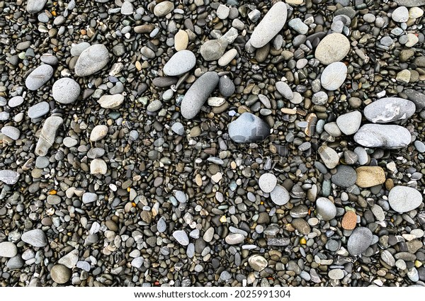 a low tide washed pebble stones beach rocks close up view with sand and shadows