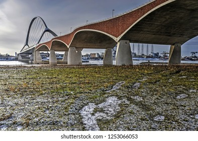 Low vegetation and a thin layer of snow in the floodplain of the river Waal near Nijmegen the Netherlands near the concrete, brick and steel arches of city bridge De Oversteek (The Crossing)