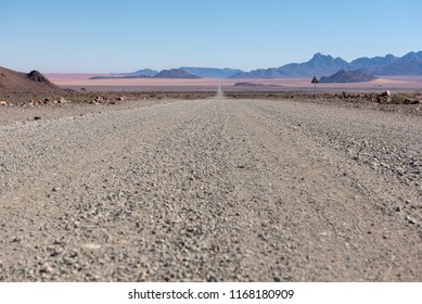 Low view angle of open gravel road to horizon in desert, Namibia