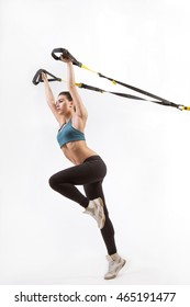 Low view of beautiful young woman training with suspension trainer sling or suspension straps isolated on white background in studio. Upper body exercise concept on TRX.