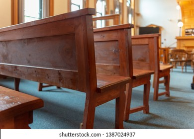A low view of the benches in a courthouse or court of law. The old wooden straight framed benches are lined up in the back of the courtroom in the witness area.  The judge's bench is in the background