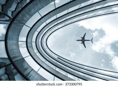 Blaues Bild mit niedriger Aussicht, modernes Architekturgebäude mit Landeflugzeug auf Hintergrund
