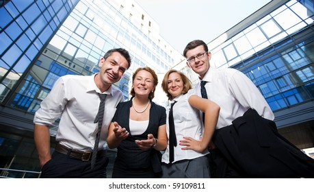 Low view of four happy business office workers staying in front of business building. Two men and two women demonstrating unity and team work.