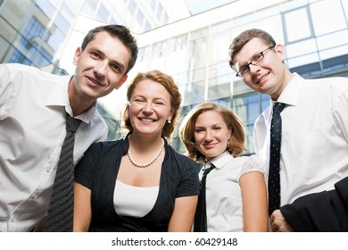 Low view of four happy office workers staying outdoors and looking at the camera. Two men and two women smiling and always working in a team.
