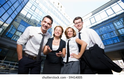 Low view of group of happy office workers staying in front of business building. Two men and two women showing unity and success outdoors.
