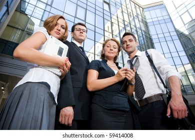 Low view of group of office workers staying outdoors and they are going to office to discuss business projects with their business partners.