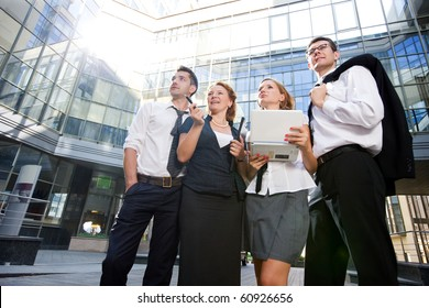 Low view of group of office workers staying outdoors after hard working day. People holding laptop computer and thinking about new business projects concerning office building.