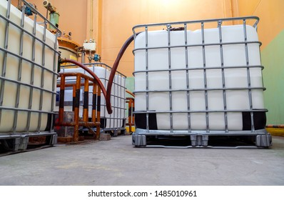 Low view inside of the factory. The large white tanks chemical packaging. Suction pipes for transferring to the main storage tank.