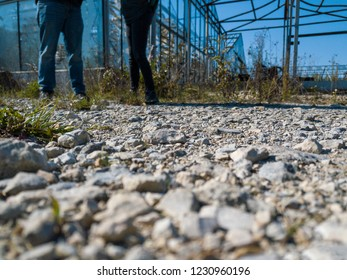 low view on feet of a couple on cobbled road against abandoned greenhouse
