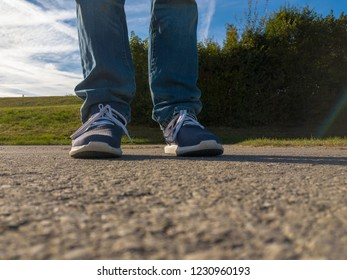 low view on man feet on cobbled road against green bushes
